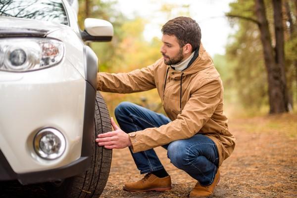 a man checking car's tires