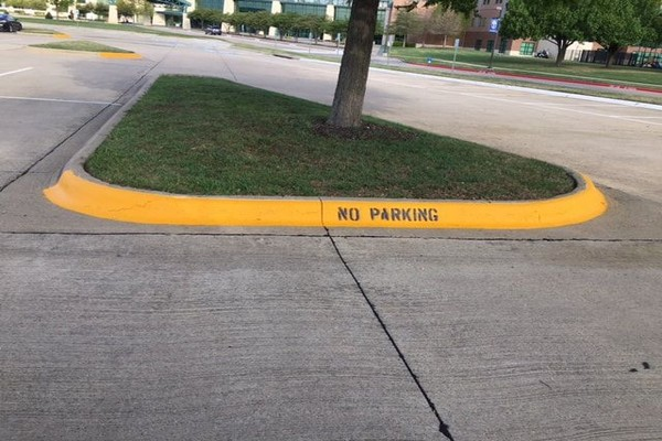 Yellow curbs with no parking sign